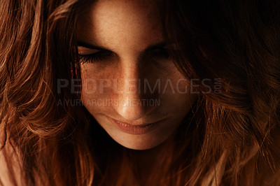 Buy stock photo A cropped closeup image of a young woman looking downwards on against a black background