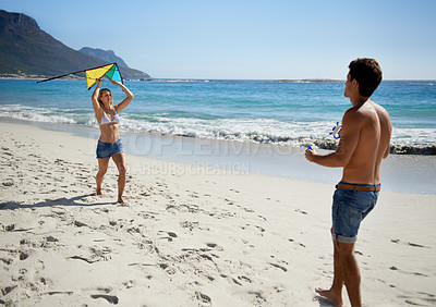 Buy stock photo A fun-loving young couple playing with a kite while enjoying a day on the beach