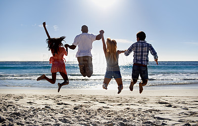 Buy stock photo Rear view of two young couple jumping together on the beach