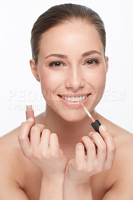 Buy stock photo Cropped portrait of a gorgeous young woman applying lipgloss with a smile