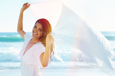 Buy stock photo Beautiful young woman holding up a sarong as the wind catches it