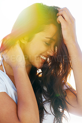 Buy stock photo A pretty woman touching her hair while smiling