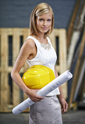 Buy stock photo A gorgeous young woman holding blueprints and looking at the camera