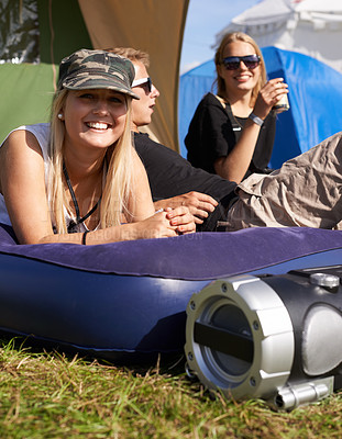 Buy stock photo Shot of a young woman relaxing on a blow up mattress at an outdoor festival