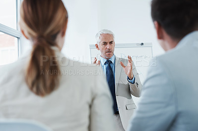 Buy stock photo Rearview shot of a mature businessman making a presentation to younger colleagues
