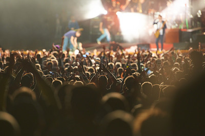 Buy stock photo Rear view shot of a packed audience watching a great musical act with their hands raised