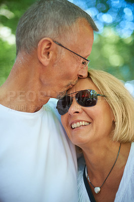 Buy stock photo Shot of an affectionate mature couple at an outdoor festival