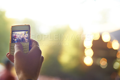Buy stock photo Cropped shot of a person taking a photo with their phone at an outdoor festival