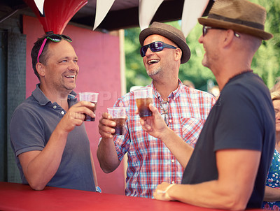 Buy stock photo Cropped shot of three male friends drinking at a festival