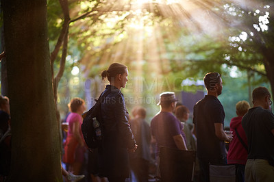 Buy stock photo A group of people watching a band beneath the trees at a music festival