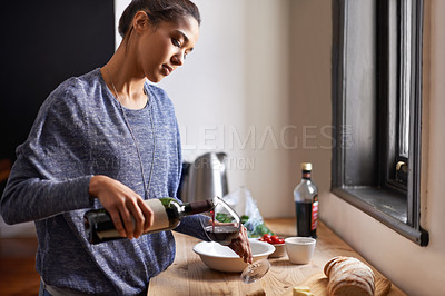 Buy stock photo A young woman pouring some red wine
