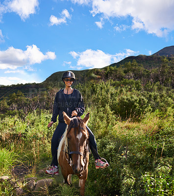Buy stock photo A young woman riding a horse