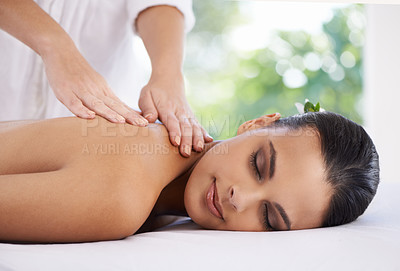 Buy stock photo Shot of a young woman enjoying a massage at a spa