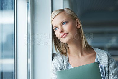 Buy stock photo A thoughtful young college student gazing out a window
