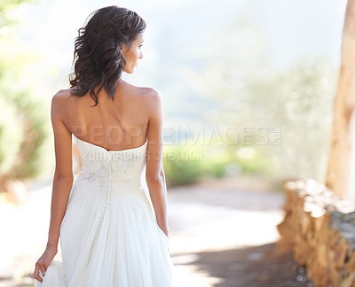 Buy stock photo A young bride looking to the side while walking down a path outside