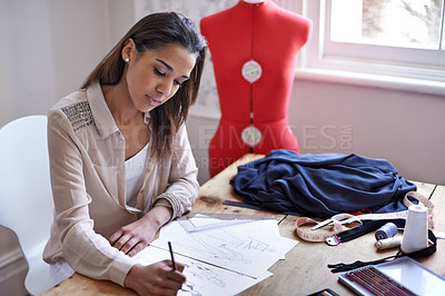 Buy stock photo A fashion designer drawing sketches in her office