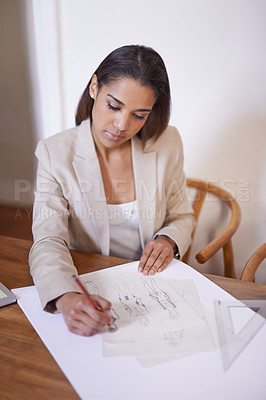 Buy stock photo A young fashion designer making sketches