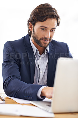 Buy stock photo A handsome businessman using his laptop