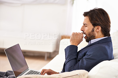 Buy stock photo A handsome businessman yawning while working on his laptop