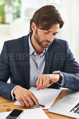 Buy stock photo A handsome businessman looking at his watch while at work