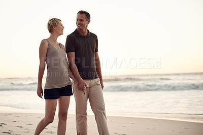 Buy stock photo Shot of a mature couple taking a walk on the beach