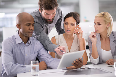 Buy stock photo Shot of a group of businesspeople discussing the contents of a tablet during a meeting