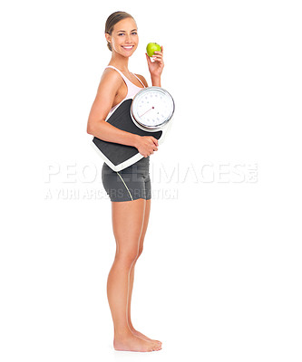 Buy stock photo full length portrait of an attractive young woman holding an apple and a weight scale