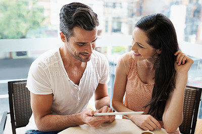 Buy stock photo Shot of a young couple using their tablet during a coffee date