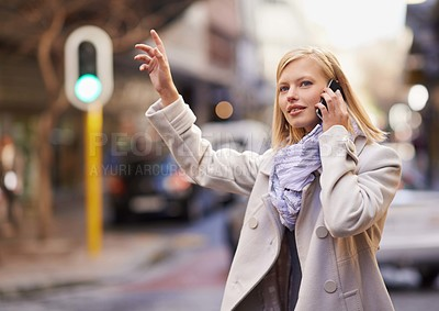 Buy stock photo Cropped shot of a young woman hailing a cab while talking on her cellphone