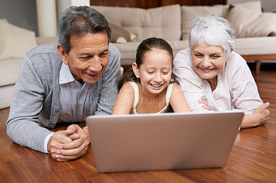 Buy stock photo A young girl and her grandparents lying on the floor looking at a laptop