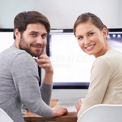 Buy stock photo Portrait of two smiling young professionals at their desk