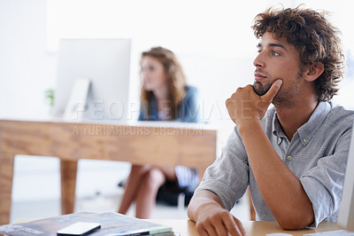 Buy stock photo A young businessman sitting at his desk looking away thoughtfully