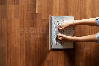 Buy stock photo Young woman using her laptop with her feet on a wooden floor with lots of copyspace