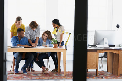 Buy stock photo Full length shot of a group of young people meeting over documents