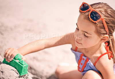 Buy stock photo Shot of a little girl building a sandcastle at the beach