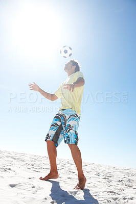 Buy stock photo Image of handsome young boy playing football at the beach