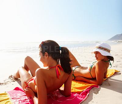 Buy stock photo Teenage girls sunbathing at the sea shore - copyspace