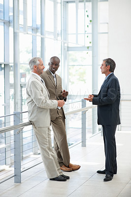 Buy stock photo Portrait of confident business people standing near a glass railing and communicating