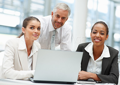 Buy stock photo Group of successful business people working together on a laptop