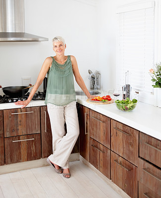 Buy stock photo Portrait of a happy mature woman standing in the kitchen