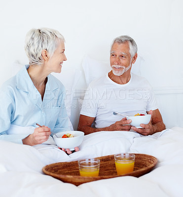Buy stock photo Cute old couple in bed having a bowl of fruits and juice