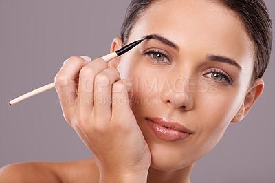 Buy stock photo Studio shot of a woman applying makeup to her eyebrow