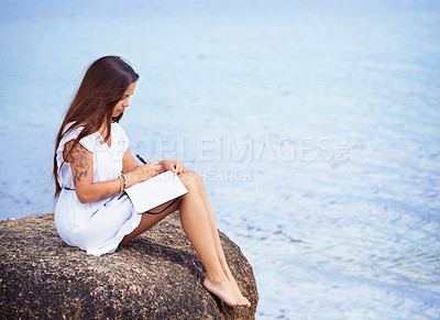 Buy stock photo Full length shot of a gorgeous tattooed young woman sitting on a rock writing in a diary