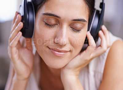 Buy stock photo Shot of a young woman listening to music while relaxing at home