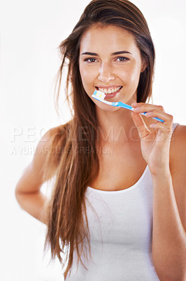 Buy stock photo A gorgeous young brunette brushing her teeth in the morning