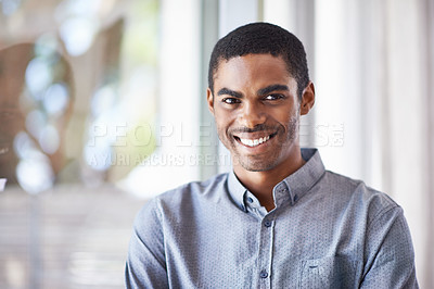 Buy stock photo Portrait of a handsome young man standing by a window in his home