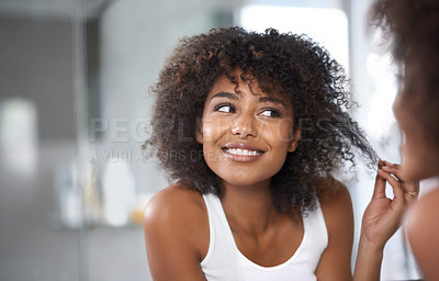 Buy stock photo Shot of an attractive young woman taking care of her hair