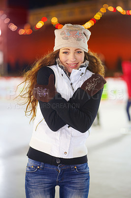 Buy stock photo A young woman standing on an ice rink on a winters day