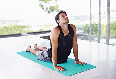 Buy stock photo A content young man doing yoga at home