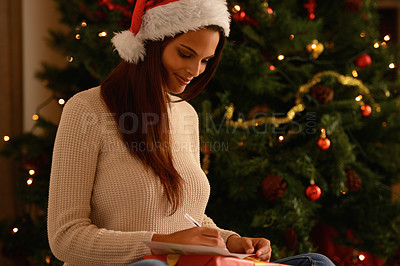Buy stock photo An attractive ethnic femal writing in front of a Christmas tree